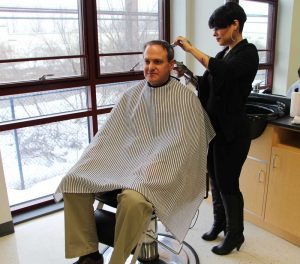 Jessica Hernandez gives barbering instructor Drew Givler a haircut in the barbershop at TCHS Brandywine.