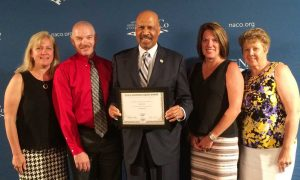 Representatives from the Chester County Intermediate Unit (CCIU) joined Chester County Commissioners' Chair Terence Farrell in accepting the National Association of Counties (NACo) Achievement Award for Employment and Training at NACo's annual conference in Long Beach, California.   Pictured from left to right are:  Dr. Jacalyn Auris and Mr. R. Scot Semple from the CCIU, County Commissioner Terence Farrell, and Laurie Masino and Dr. Anita Riccio, also from the CCIU.