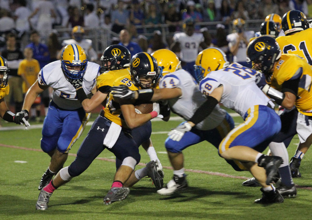 Downingtown East's dominant defensive line often was able to power through and stop run plays in the backfield against Unionville, Friday. Here, Stephen Dilulio (44) and Jack Hayward (28) close in on Jack Adams (25). Jim Gill photo.